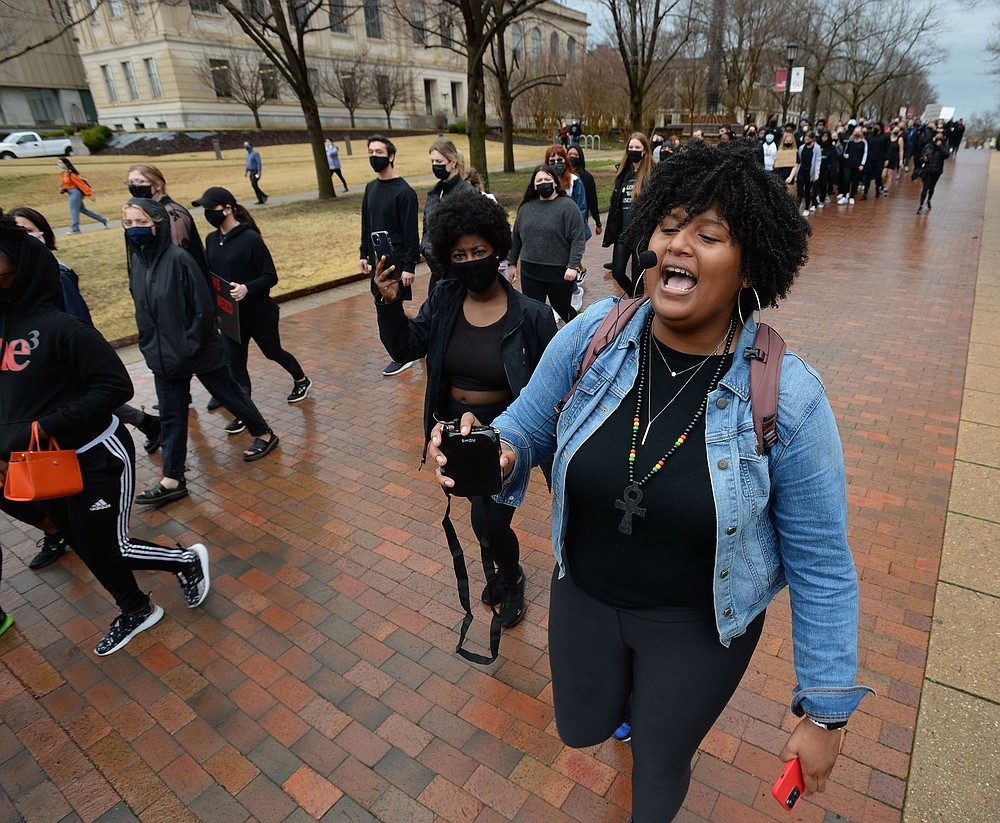 Tyrah Jackson (right) of Pine Bluff, a student at the University of Arkansas, Fayetteville, leads a group of students and members of the campus community on a march last month to call for the school to disassociate from J. William Fulbright and Charles Brough. (NWA Democrat-Gazette/Andy Shupe)