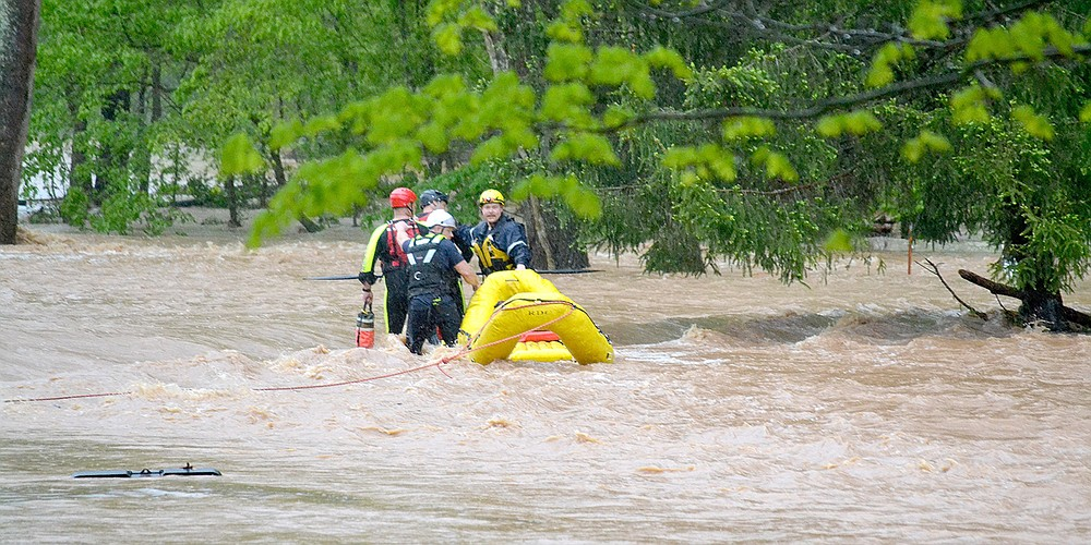 Bella Vista and Rogers Fire Department water rescue personnel assist Little Flock personnel in rescuing two men from floodwaters on Rustic Drive in Little Flock. They also rescued five people and two dogs from a residence on that street. More photos at arkansasonline.com/429/nwarain/.
