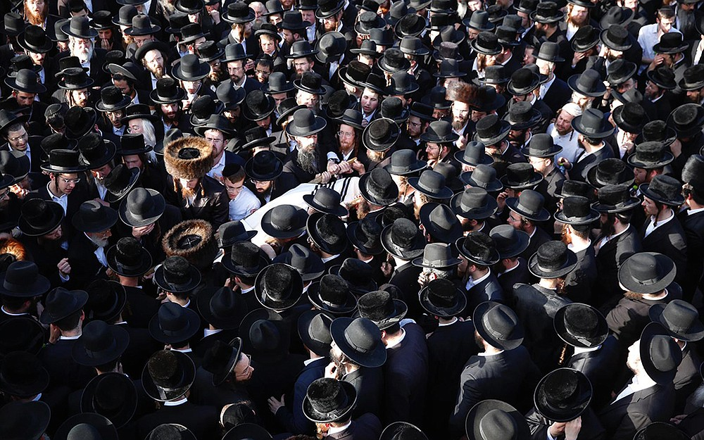 Mourners carry the body of Shragee Gestetner, a Canadian singer who died during Lag BaOmer celebrations at Mount Meron in northern Israel, at his funeral Friday in Jerusalem. A stampede at a religious festival attended by tens of thousands of ultra-Orthodox Jews killed dozens of people and injured about 150 early Friday, medical officials said. More photos at arkansasonline.com/51lagbaomer/. (AP/Ariel Schalit)