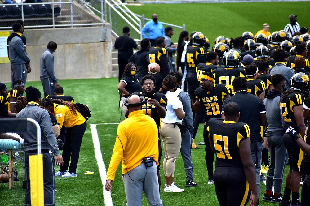 UAPB quarterback Skyler Perry warms up on the sideline with quarterbacks coach Kenton Evans during an April 17 home game against Prairie View A&M.  (Pine Bluff Commercial/I.C. Murrell)