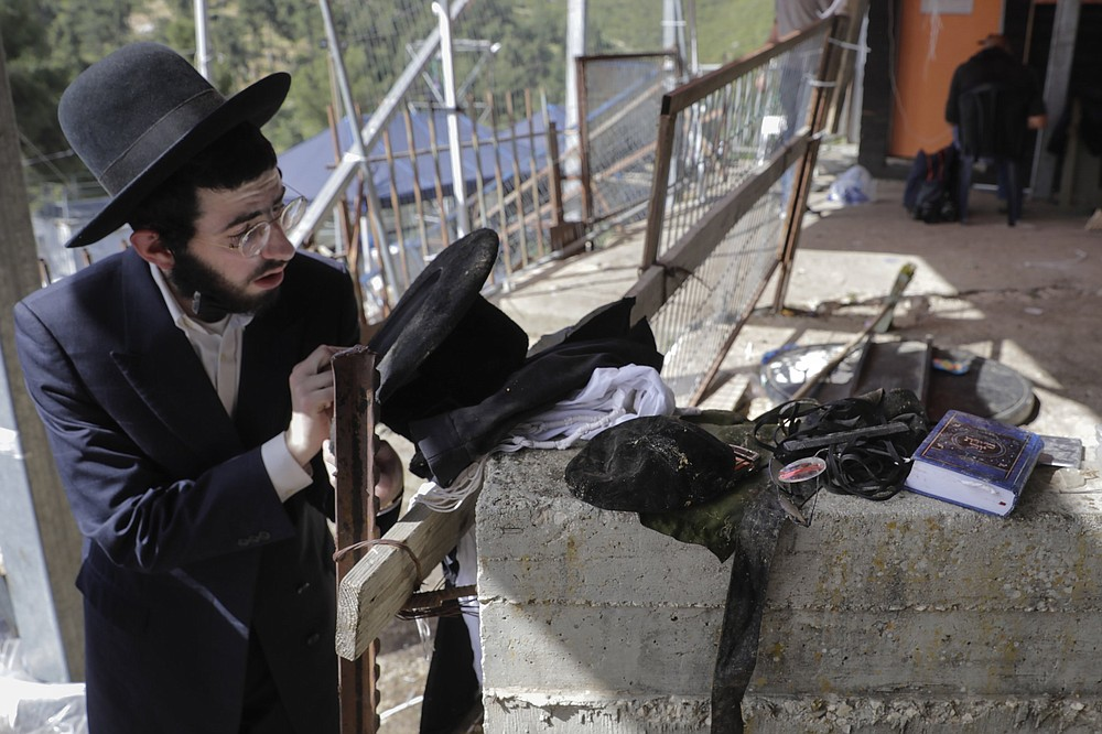 An ultra-Orthodox Jewish man examines personal belongings left Friday at the site of a stampede at the Lag BaOmer festival at Mt. Meron, Israel. (AP/Sebastian Scheiner)