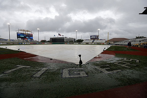 A tarp covers the field during a rain delay before an NCAA college regional baseball game between Utah Valley and LSU in Baton Rouge, La., Friday, June 3, 2016. (AP Photo/Gerald Herbert)