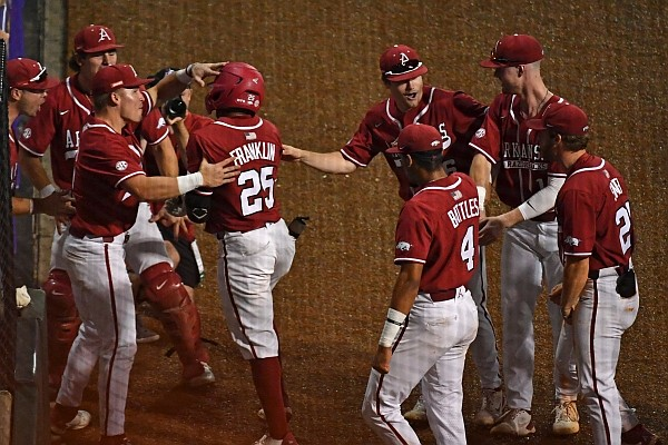 Arkansas center fielder Christian Franklin is greeted by teammates outside of the Razorbacks' dugout after hitting a home run during a game against LSU on April 30, 2021, in Baton Rouge, La.