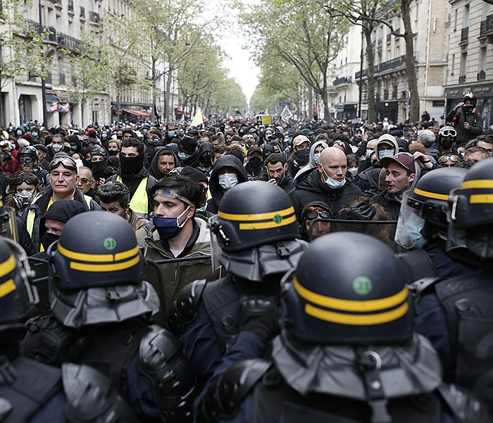 Riot police officers face off with demonstrators Saturday at a May Day march in Paris. Despite the pandemic, crowds around the world turned out, or were turned away, during the annual celebration of workers' rights. More photos at arkansasonline.com/52mayday21/. (AP/Lewis Joly)