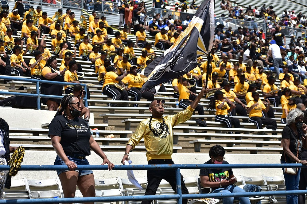 A UAPB fan waves a flag as he dances during Saturday's Southwestern Athletic Conference Championship Game at Mississippi Veterans Memorial Stadium in Jackson, Miss. An announced crowd of 17,248 attended the game, which was the culmination of a spring season brought on by the coronavirus pandemic that canceled the 2020 slate. (Pine Bluff Commercial/I.C. Murrell)