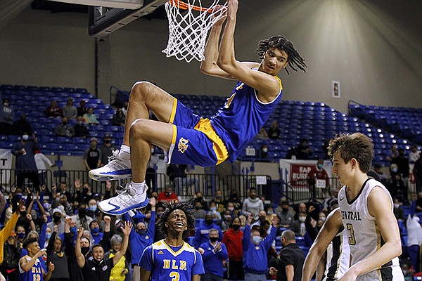 North Little Rock's Kel'el Ware (10) hangs on the rim after a dunk during the fourth quarter of the Charging Wildcats' 65-55 win in the Class 6A boys state championship game on Thursday, March 18, 2021, at Bank OZK Arena in Hot Springs.