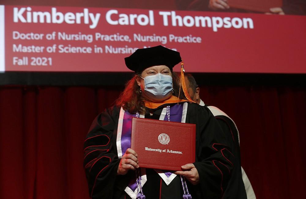 Kimberly Carol Thompson receives her diploma Thursday during the University of Arkansas 2021 graduate degree commencement ceremony at Bud Walton Arena in Fayetteville. (NWA Democrat-Gazette/David Gottschalk)