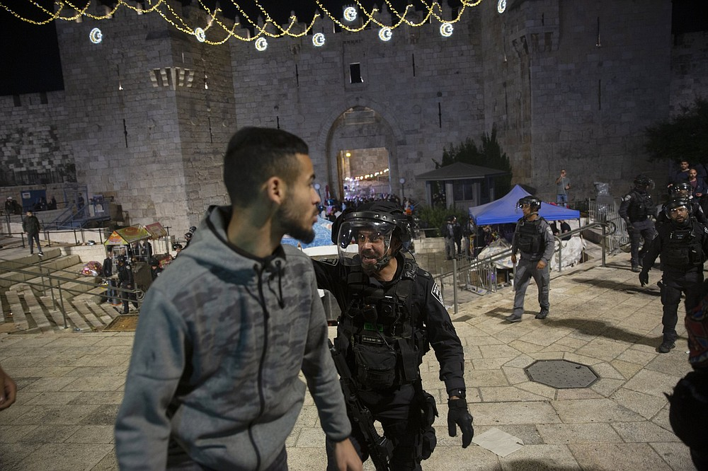 An Israeli policeman shouts Friday at a Palestinian man to leave the Damascus Gate to the Old City of Jerusalem after clashes at the Al-Aqsa Mosque compound. (AP/Maya Alleruzzo)