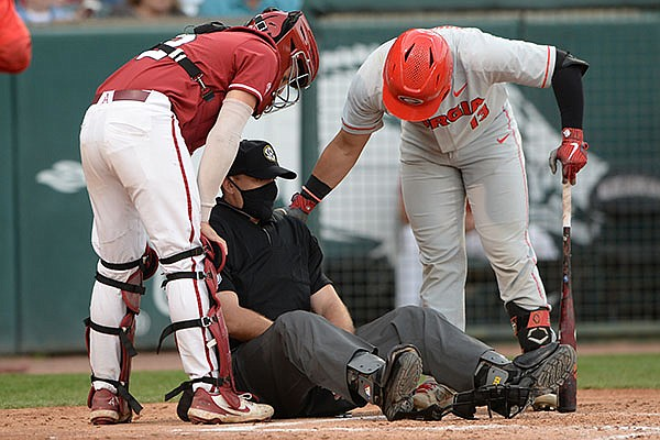 Arkansas catcher Casey Opitz (left) and Georgia designated hitter Fernando Gonzalez (right) check on home plate umpire Ronnie Teague after Teague was hit in the mask with a foul ball during a game Saturday, May 8, 2021, in Fayetteville.