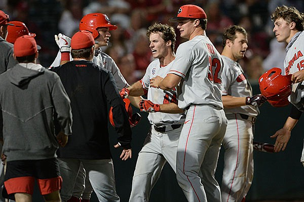 Georgia center fielder Ben Anderson (44) is congratulated by teammates after he hit a home run during the seventh inning of a game against Arkansas on Saturday, May 8, 2021, in Fayetteville.