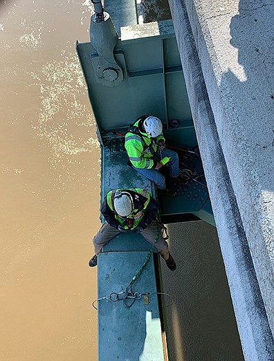 Workers from the Arkansas and Tennessee transportation departments inspect the cracked beam Wednesday on the Interstate 40 Mississippi River bridge between West Memphis and Memphis. The break is just in front of the worker straddling the beam. (Special to the Arkansas Democrat-Gazette)
