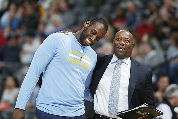 Denver Nuggets center JJ Hickson, left, jokes with Miami Heat assistant coach Keith Smart during the second half of an NBA basketball game Friday, Jan. 15, 2016, in Denver. Miami won 98-95. (AP Photo/David Zalubowski)