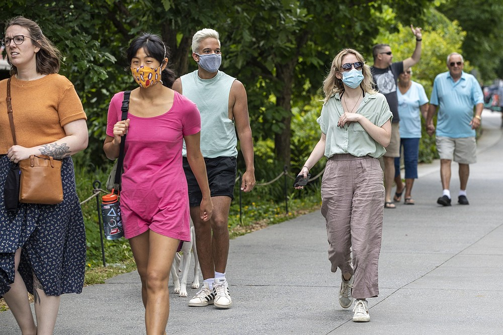 Madeline Raskay (right) and Aldany Diaz (third from left) wear masks while out walking Friday in Atlanta. Both said they are fully vaccinated but still prefer to mask up in public. More photos at arkansasonline.com/515covid19/. (AP/Atlanta Journal-Constitution/Alyssa Pointer)