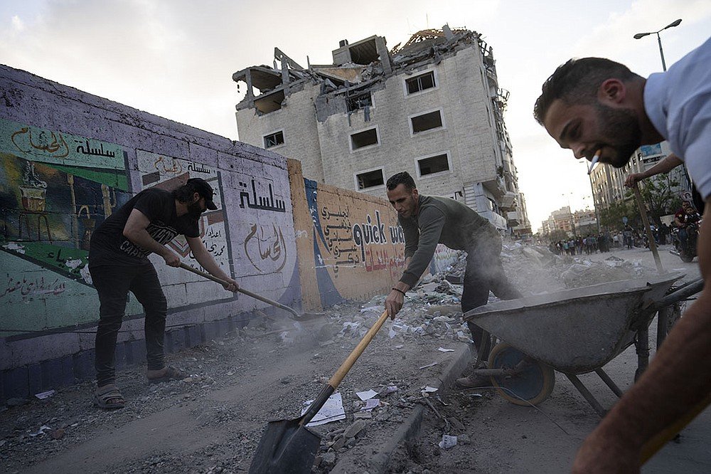 """People clean the streets of debris Friday in Gaza City. """"Life will return, because this is not the first war, and it will not be the last war,"""" said shop owner Ashraf Abu Mohammad. While assessing the damage, Gazans celebrated what some claimed was a victory of endurance over a powerful enemy. (AP/John Minchillo)"""