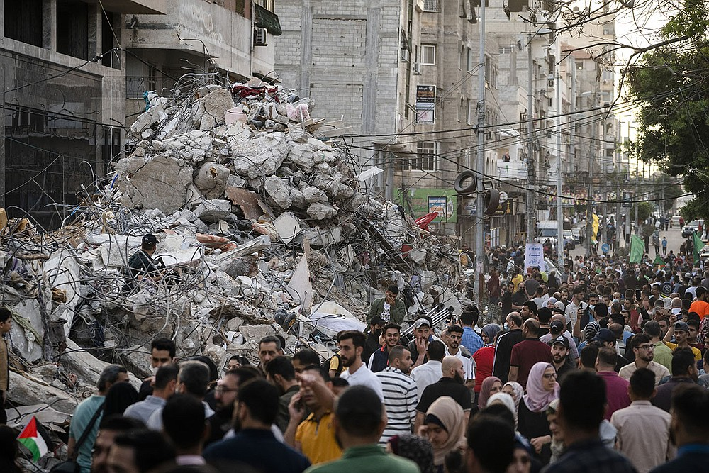 Gaza residents walk past a bombed-out building Friday after the cease-fire between Gaza's Hamas rulers and Israel took effect. The Gaza Health Ministry says at least 243 Palestinians were killed, including 66 children, and 1,910 people were wounded in the 11 days of fighting. (AP/John Minchillo)