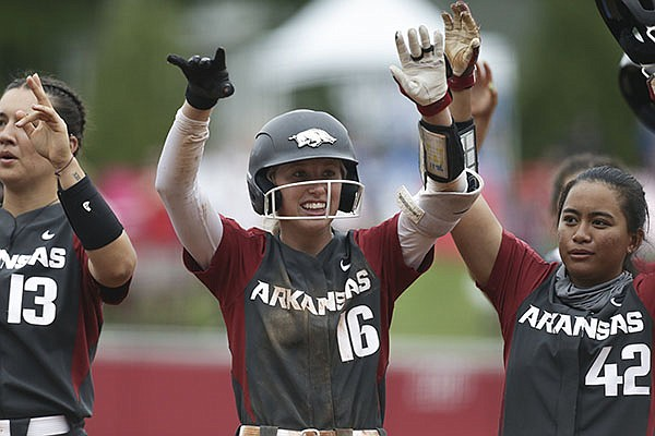 Arkansas softball players Kayla Green (13), Keely Huffine (16) and Sam Torres (42) celebrate after defeating Manhattan 8-0 during an NCAA regional game Friday, May 21, 2021, in Fayetteville.