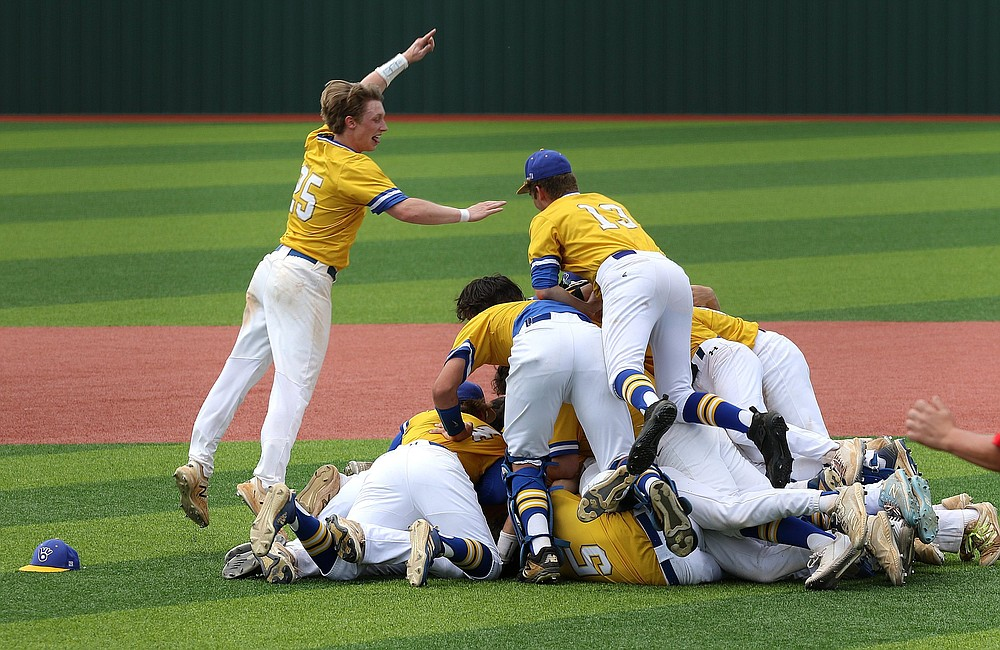 Valley View's Wil French (left) leaps on to the pile of his teammates after the Blazers' 8-1 victory over Magnolia in the Class 4A state championship game Saturday. It was the third state title for Valley View. More photos at www.arkansasonline.com/523baseball/ (Arkansas Democrat-Gazette/Thomas Metthe)