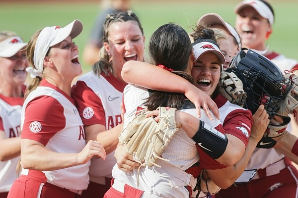 Arkansas pitcher Mary Haff (4) hugs catcher Kayla Green (13) as they celebrate with teammates on Sunday, May 23, 2021, during the NCAA Fayetteville Softball Regional at Bogle Park in Fayetteville. Check out nwaonline.com/210524Daily/ for the photo gallery.