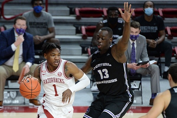 Arkansas forward JD Notae (1) drives along the baseline Saturday, Dec. 12, 2020, ahead of Central Arkansas forward Eddy Kayouloud (13) during the first half of play in Bud Walton Arena in Fayetteville.