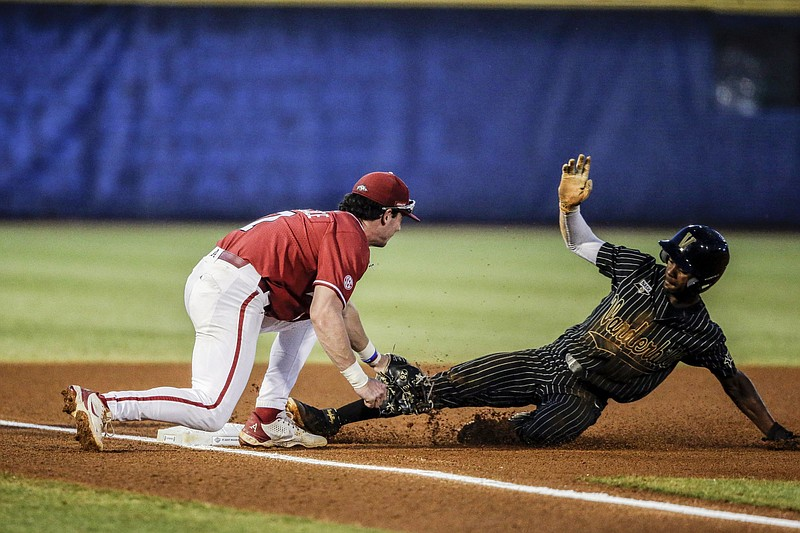 Vanderbilt's Enrique Bradfield Jr. (51) is tagged out by Arkansas third baseman Cayden Wallace (7) as he slides into third base during the first inning of an NCAA college baseball game during the Southeastern Conference tournament Thursday, May 27, 2021, in Hoover, Ala. (AP Photo/Butch Dill)