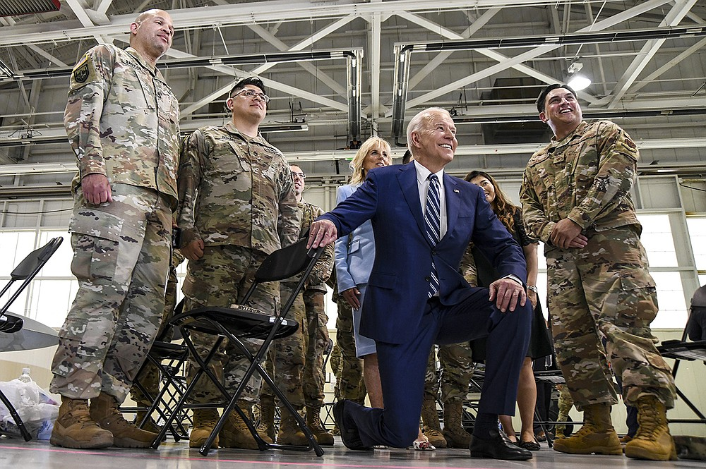President Joe Biden poses with service members Friday at Joint Base Langley Eustis in Hampton, Va., where he acknowledged the unheralded sacrifices made by service members and their families, and delivered an emotional remembrance of his son Beau, a veteran. (The New York Times/Kenny Holston)
