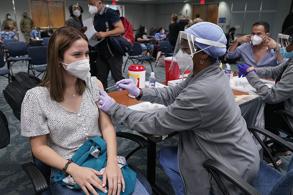 Natalia Dubom of Honduras gets a Johnson & Johnson covid-19 shot Friday at Miami International Airport. The vaccine was offered to all arriving passengers. Florida's Emergency Management Agency is running the program through Sunday. (AP/Marta Lavandier)