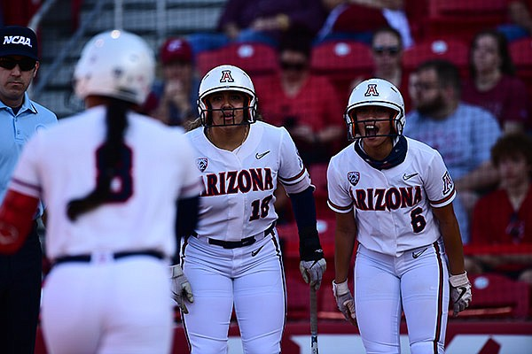 Arizona's Sharlize Palacios (18) and Janelle Meoño (6) wait as Dejah Mulipola (8) runs toward home plate after Mulipola hit a home run during an NCAA super regional game against Arkansas on Friday, May 28, 2021, in Fayetteville.