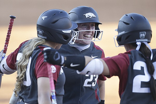 Arkansas outfielder Hannah McEwen (23) is greeted by teammates after she hit a home run during an NCAA super regional game against Arizona on Friday, May 28, 2021, in Fayetteville.