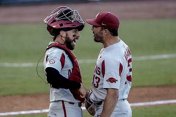 Arkansas catcher Casey Opitz, left, celebrates with pitcher Connor Noland (13) after the team's 3-2 win over Ole Miss in an NCAA college baseball game during the Southeastern Conference tournament Saturday, May 29, 2021, in Hoover, Ala. (AP Photo/Butch Dill)