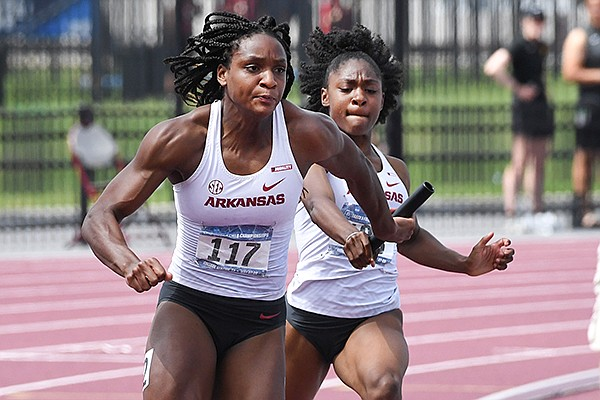 Arkansas sprinter Tiana Wilson (left) takes the baton from Jayla Hollis in the 400-meter relay during the NCAA West Prelims on Saturday, May 29, 2021, in College Station, Texas.