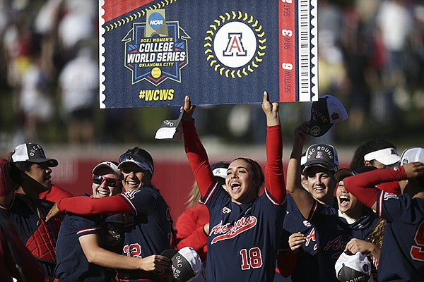 Arizona catcher Sharlize Palacios (18) holds up a Women's College World Series poster, Saturday, May 29, 2021, after the Wildcats defeated Arkansas 4-1 in Fayetteville.