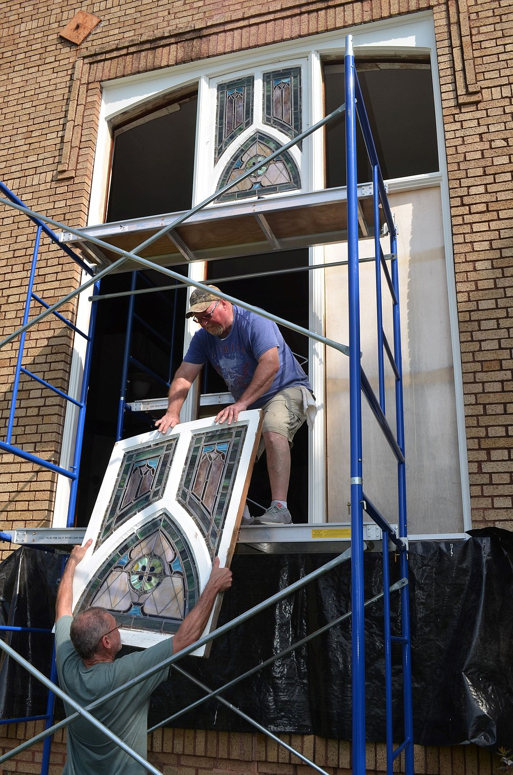 Ron Dwarshak (top) and Nathan Cathey reinstall the stained-glass windows at the former Fordyce Presbyterian church.  (Special to The Commercial/Richard Ledbetter)