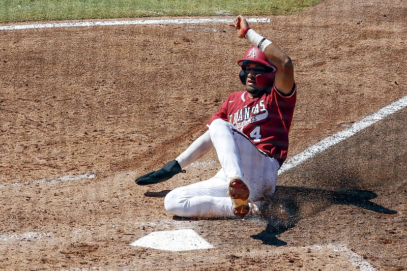Arkansas' Jalen Battles slides safely into home plate in the fifth inning of an NCAA college baseball championship game against Tennessee during the Southeastern Conference tournament Sunday, May 30, 2021, in Hoover, Ala. (AP Photo/Butch Dill)