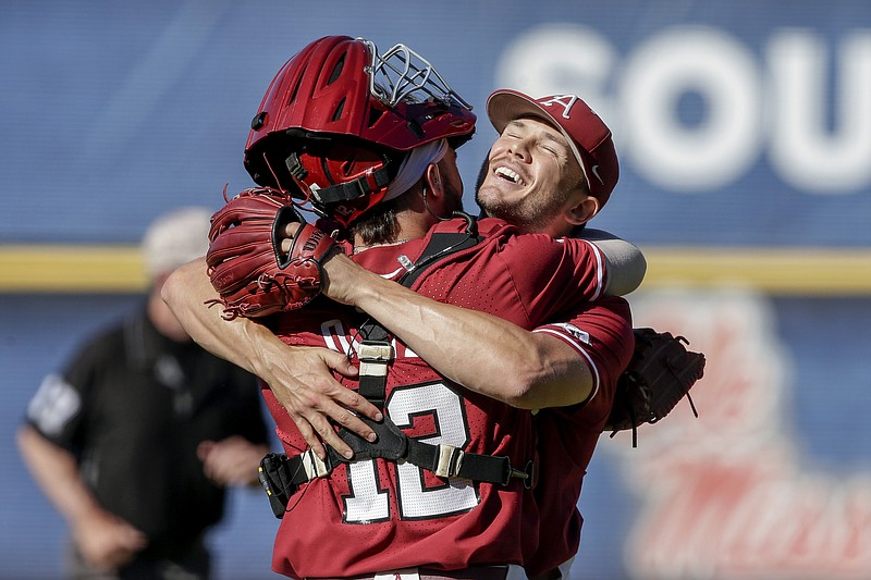 Arkansas catcher Casey Opitz (12) celebrates with pitcher Kevin Kopps after they defeated Tennessee to win the NCAA college baseball championship game during the Southeastern Conference tournament Sunday, May 30, 2021, in Hoover, Ala. (AP Photo/Butch Dill)