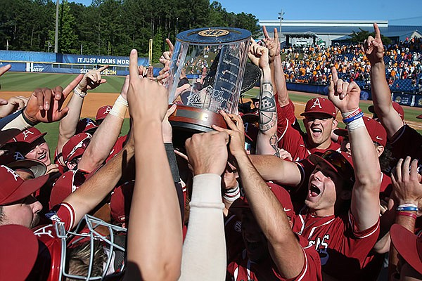 Arkansas players hoist the SEC Tournament championship trophy after defeating Tennessee 7-2 on Sunday, May 30, 2021, in Hoover, Ala. (SEC pool photo)