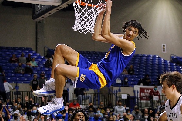 North Little Rock's Kel'el Ware hangs on the rim after a dunk during the fourth quarter of the Charging Wildcats' 65-55 victory over Little Rock Central in the Class 6A championship Thursday at Bank OZK Arena in Hot Springs. (Arkansas Democrat-Gazette/Thomas Metthe)