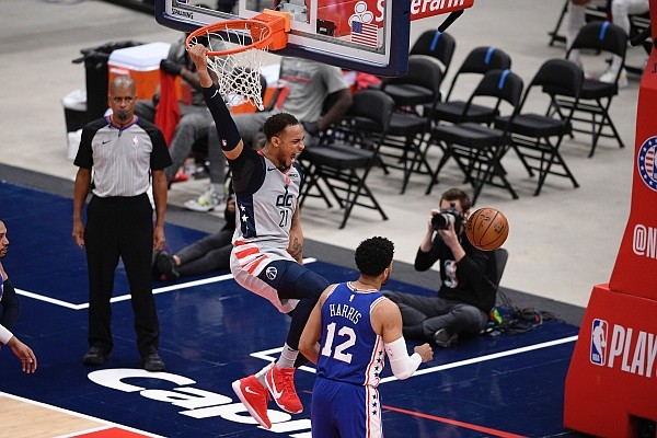 Washington Wizards center Daniel Gafford (21) hangs from the rim after a dunk next to Philadelphia 76ers forward Tobias Harris (12) during the second half of Game 4 in a first-round NBA basketball playoff series, Monday, May 31, 2021, in Washington. (AP Photo/Nick Wass)