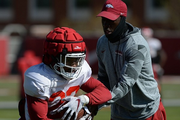 Arkansas assistant coach Jimmy Smith hands the ball off to running back Josh Oglesby.
