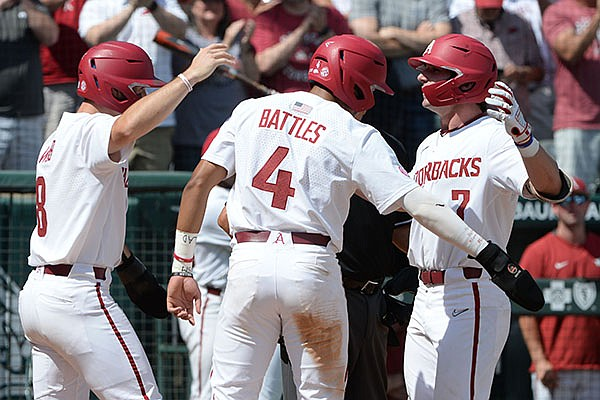 Arkansas third baseman Cayden Wallace (7) is congratulated at the plate Friday, June 4, 2021, after hitting a three-run home run by left fielder Braydon Webb (left) and shortstop Jalen Battles (4) during the fourth inning of the Razorbacks' 13-8 win over NJIT in the first game of the NCAA Fayetteville Regional at Baum-Walker Stadium in Fayetteville.