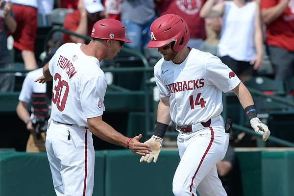 Arkansas first baseman Cullen Smith (14) is congratulated by assistant coach Nate Thompson Friday, June 4, 2021, after hitting a solo home run during the fourth inning of the Razorbacks' 13-8 win over New Jersey Institute of Technology in the first game of the NCAA Fayetteville Regional at Baum-Walker Stadium in Fayetteville. Visit nwaonline.com/210605Daily/ for the photo gallery.