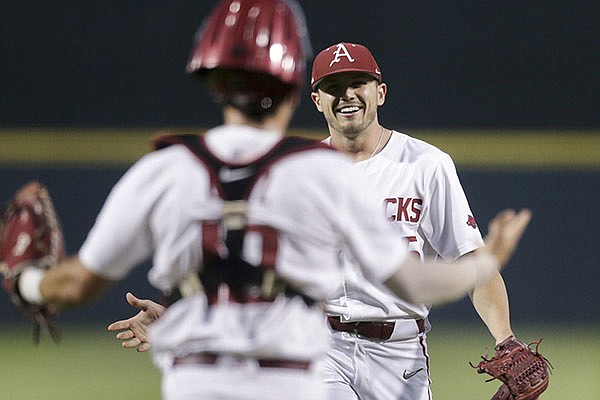 Arkansas pitcher Kevin Kopps (facing) is greeted by catcher Casey Opitz after the Razorbacks recorded the final out of an NCAA regional game against Nebraska on Monday, June 7, 2021, in Fayetteville.