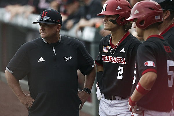 Nebraska coach Will Bolt (left) talks with players during an NCAA regional game against Arkansas on Monday, June 7, 2021, in Fayetteville.