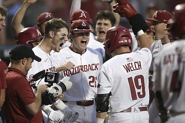 Arkansas pinch hitter Charlie Welch (19) is congratulated by teammates after he hit a home run during the ninth inning of an NCAA regional game against Nebraska on Monday, June 7, 2021, in Fayetteville.