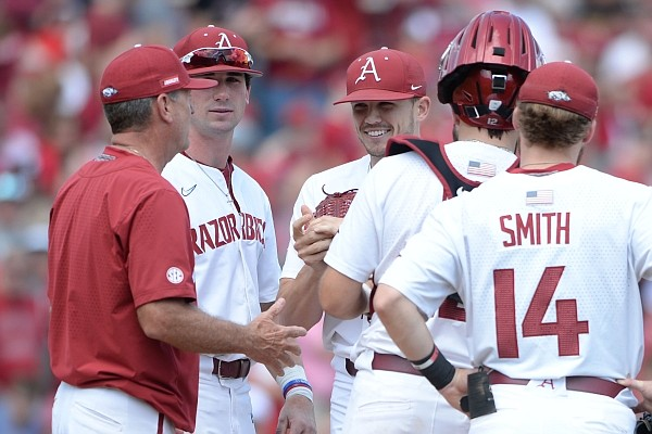 Arkansas coach Dave Van Horn (left) speaks Friday, June 4, 2021, with reliever Kevin Kopps as he enters the game with two outs in the fourth inning of the Razorbacks' 13-8 win over New Jersey Institute of Technology.