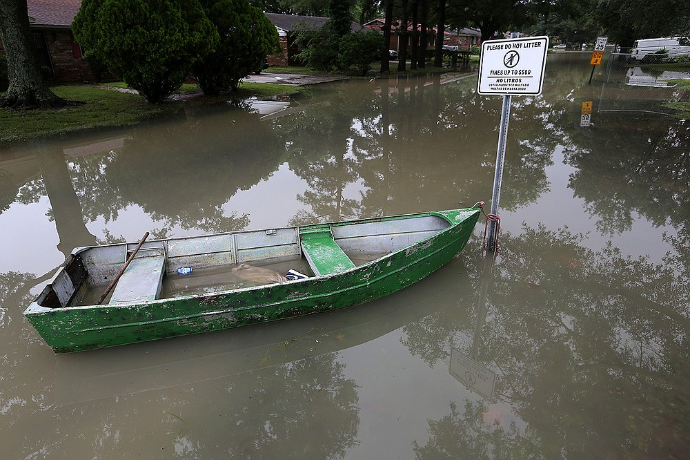 A boat sits tied to a sign Wednesday on a street in Dumas. About 300 businesses in the city have flooded, according to the county judge for Desha County. (Arkansas Democrat-Gazette/Thomas Metthe)