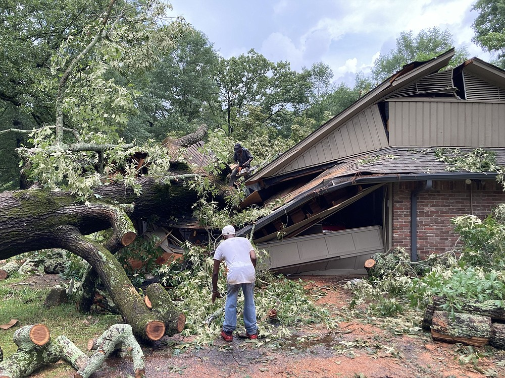 Workers with Sylvester Parker Tree Cutting Service work Wednesday to remove one of two trees that fell on this home on Cherry Street.  (Pine Bluff Commercial/Byron Tate)