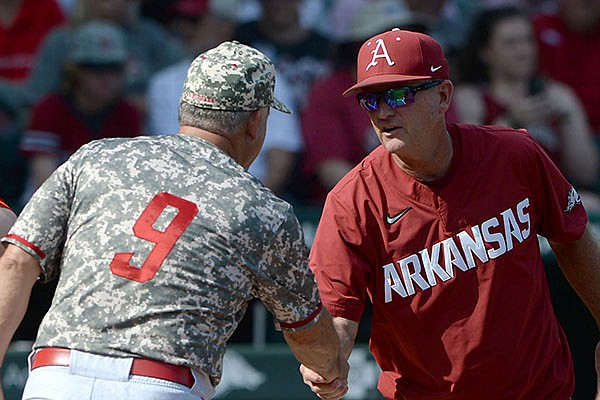 Arkansas coach Dave Van Horn (facing) shakes hands with North Carolina State coach Elliott Avent prior to an NCAA super regional game Friday, June 11, 2021, in Fayetteville.