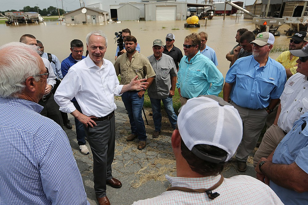 Gov. Asa Hutchinson talks with farmers Friday at the WinCott Gin Co. in Tillar after listening to their stories about crop damage during his tour of flooding in southeast Arkansas. (Arkansas Democrat-Gazette/Thomas Metthe)