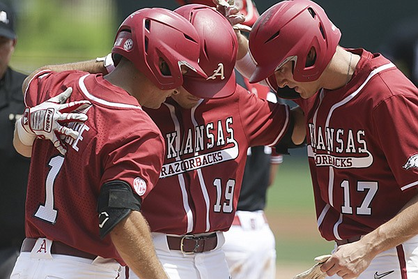 Arkansas' Charlie Welch (19) celebrates with Robert Moore (1) and Brady Slavens (17) after Welch hit a home run during an NCAA super regional game against North Carolina State on Saturday, June 12, 2021, in Fayetteville.