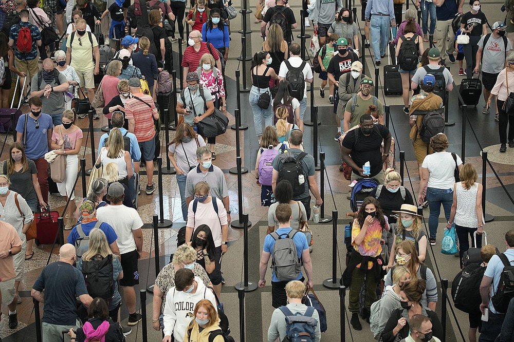 Travelers wait to pass through the south security checkpoint Wednesday at Denver International Airport. While some states are seeing a drop in coronavirus cases, cases are surging in places such as Texas and Missouri, where vaccination rates are low. (AP/David Zalubowski)